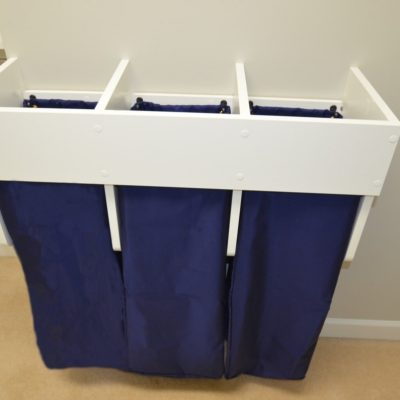 Close up peek at our (not yet!) dirty laundry sorter.  Three drawstring bags lift off of internal hooks for convenience.