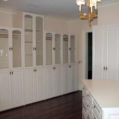 Cabinets deep enough for hanging clothes behind arched top glass doors / solid raised panel doors are punctuated by a 10' tall middle shelf unit.  Antique white laminates offer a subdued look in a large dressing room.