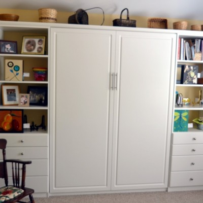 """""""Artist in residence.""""  One of many repeat clients, this professional artist was creating in a laundry room when she """"downsized.""""  We out-placed the rarely used guest suite and up-fit a beautiful wall bed and staggered side cabinets.  The opposite wall carries an art shelf for work in progress."""